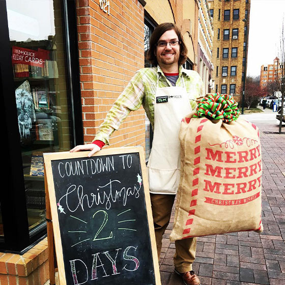Paper Source Employee with festive holiday props.