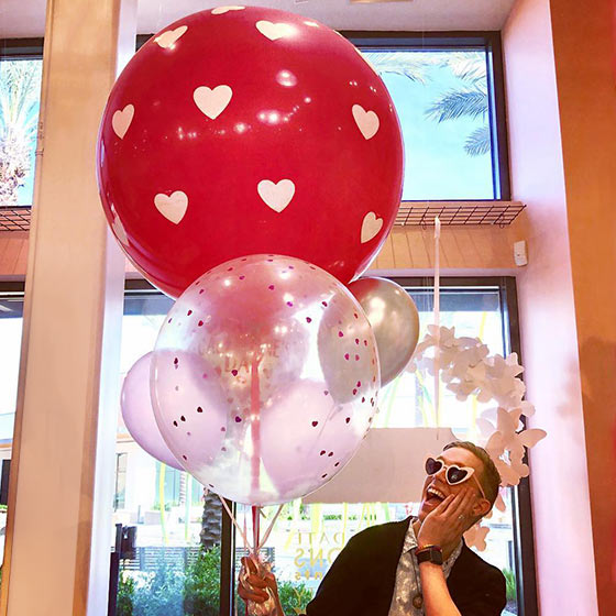 person holding valentine balloons