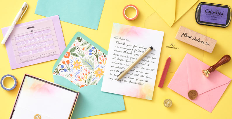 Assorted letter writing supplies, a handwritten letter and envelopes on a bright yellow background.