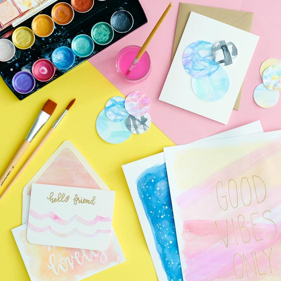 Watercolor supplies strewn about beautiful watercolor painted stationery and signs