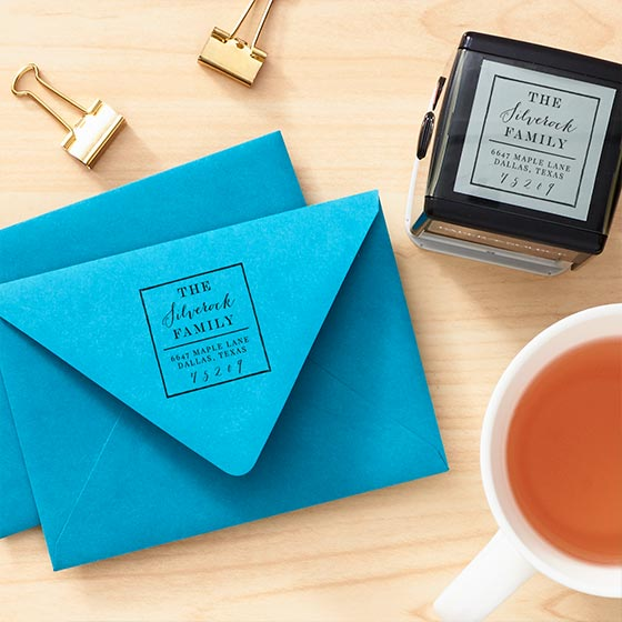 Custom Stamp Tool shown with an impression on a blue envelope