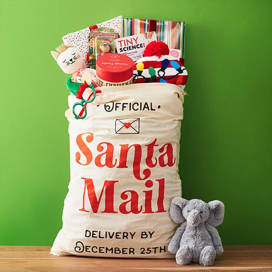 Gifts stuffed into a large bag that reads, Santa Mail.