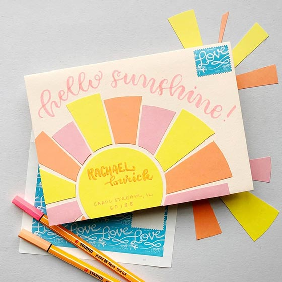 Bright and colorful custom embellished envelope. Paper has been layered on top to create a sun with rays.