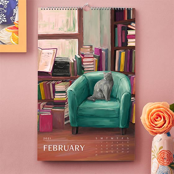 Wall Art Calendar by Paper Source featuring the month February that has an illustrated scene of a grey cat sitting on a chair surrounded by books
