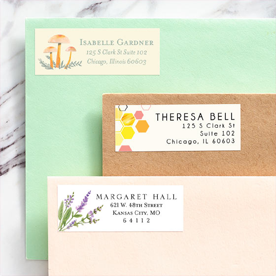 Three brightly colored envelopes that feature customizable address labels shown with mushroom, honeycomb and floral designs.