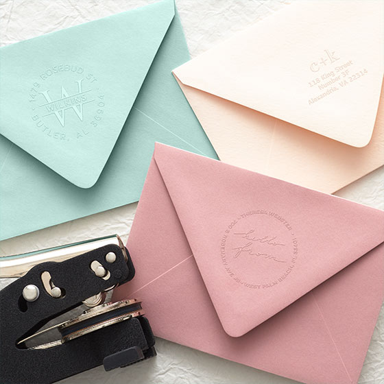 Customizable Embosser Tool and Embossing Shown on blush, rose, and eucalyptus colored envelopes.