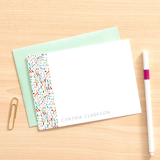 Colorful dots design on customizable stationery by Paper Source, displayed on top of a mint envelope next to a pen.