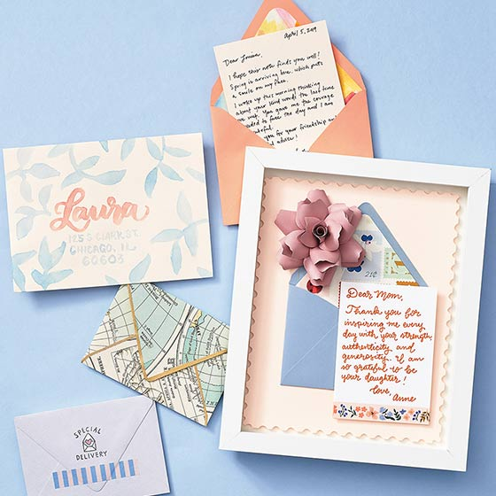 Various envelopes customized with embellishments like stamps, pens and paper.