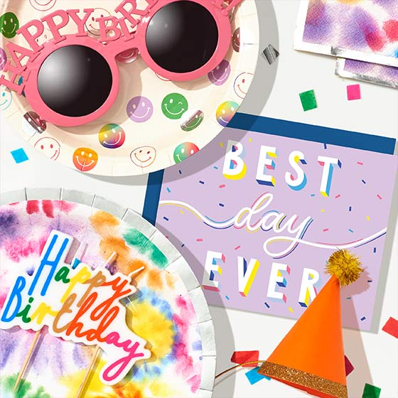 Assorted birthday party supplies including a cake topper and colorful party decor.