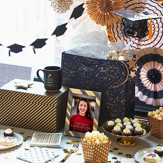 Assorted black and gold party decorations and gifts for graduates.