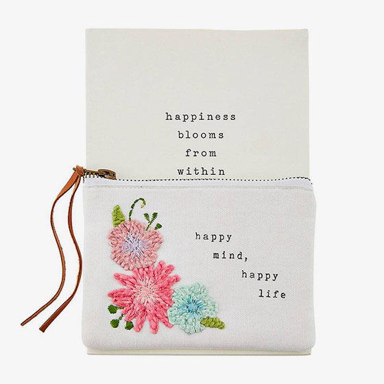Printed canvas pouch features hand-embroidered florals with French knot detail and genuine leather zipper pull that reads, Happiness Blooms from Within.