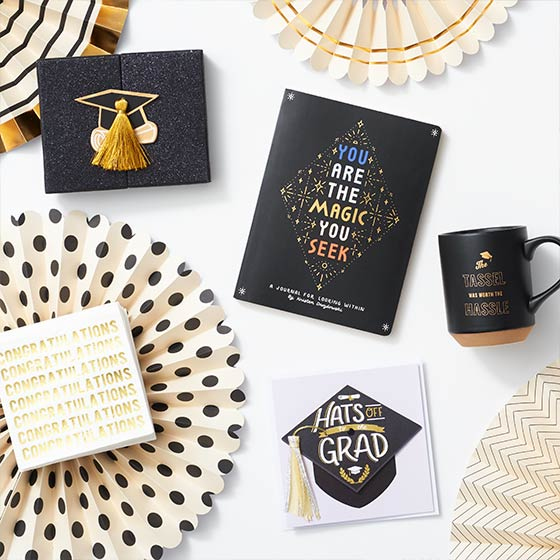 Assorted black and gold themed graduation gifts including a gift card box, journal and mug.