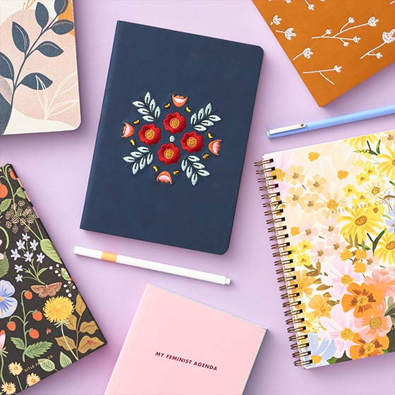 Colorful journals and notebooks with floral patterns.