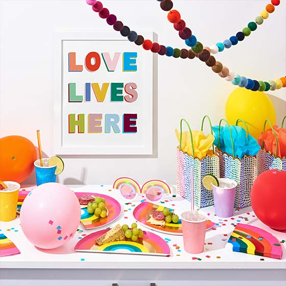 Colorful party decorations including an art print that reads, Love Lives Here.