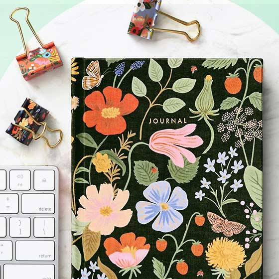 Colorful journal with floral pattern displayed with coordinating binder clips.