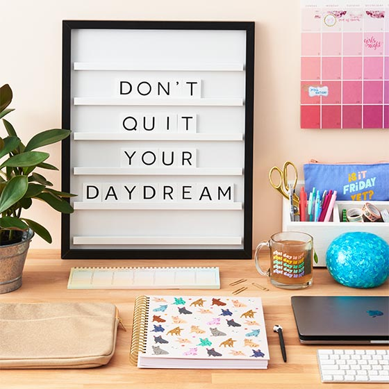 Shot of a desk with dorm essentials including a letter board that reads, don't quit your daydream.