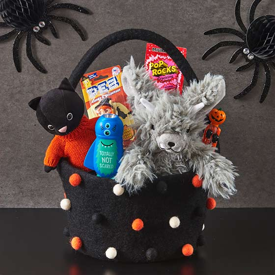 Pom basket filled with Halloween treats and goodies.