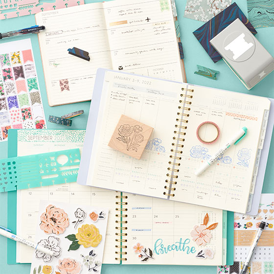Opened planners styled with accessories like washi tape and stickers.
