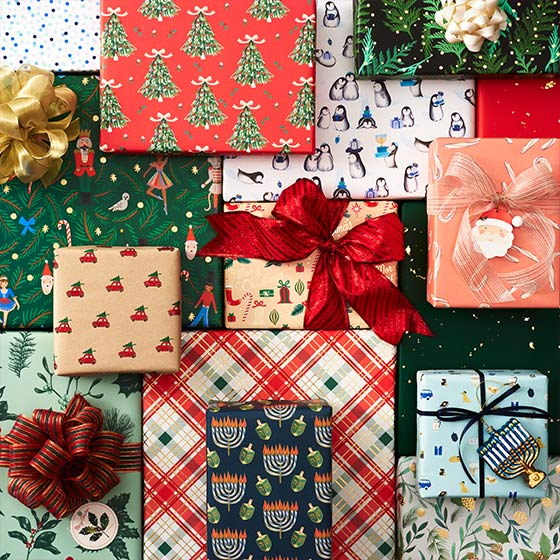 A group of differently sized boxes wrapped in decorative and festive holiday wrapping paper.