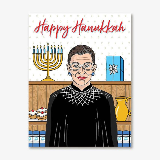 Hanukkah Greeting Card features a graphic of Supreme Court Justice Ruth Bader Ginsburg surrounded by Hanukkah festivities.